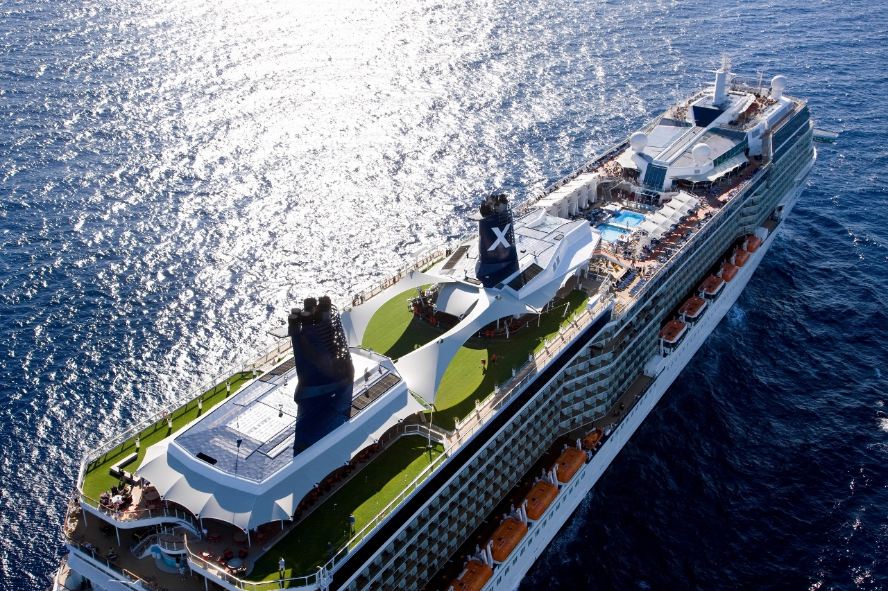 The hump of Celebrity Solstice can be seen in the middle of the ship between the lifeboats aboard the Celebrity Cruises vessel