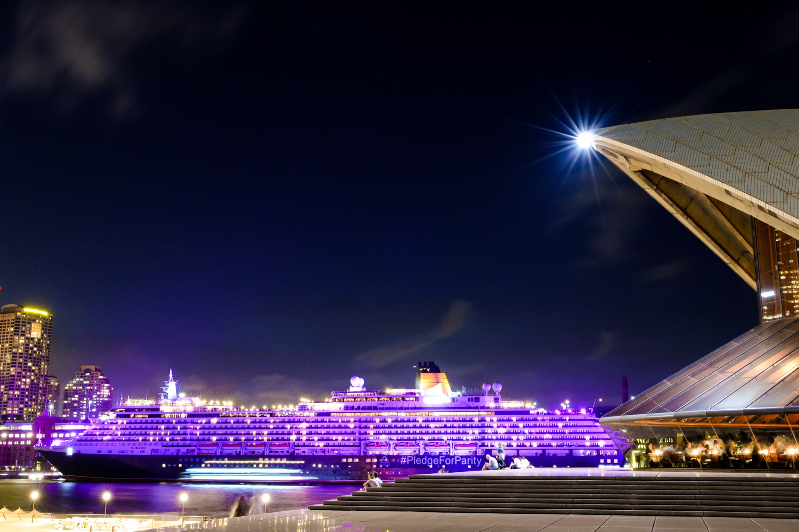 Queen Victoria bathed in purple from the Sydney Opera House.