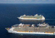 Two Royal Caribbean ships sail together side by side.