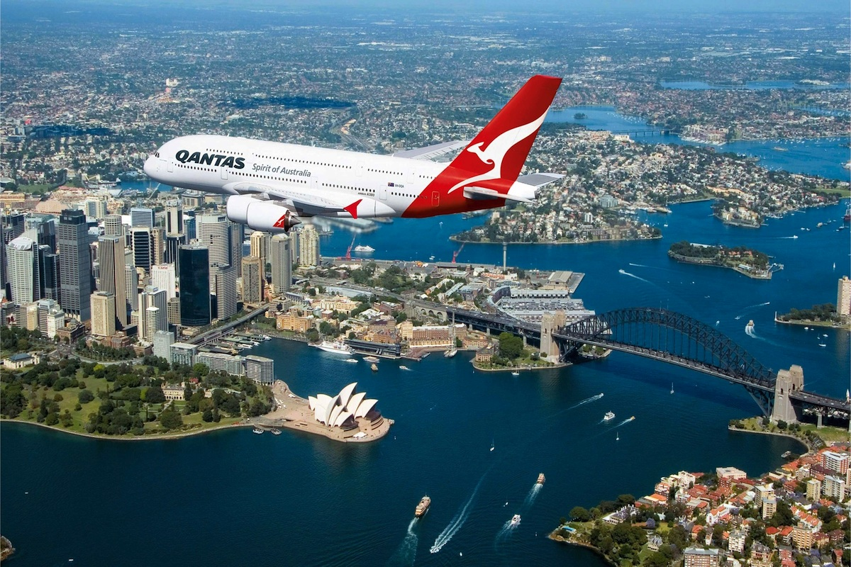 A Qantas A380 flying over the Overseas Passenger Terminal and Sydney Harbour one sunny day