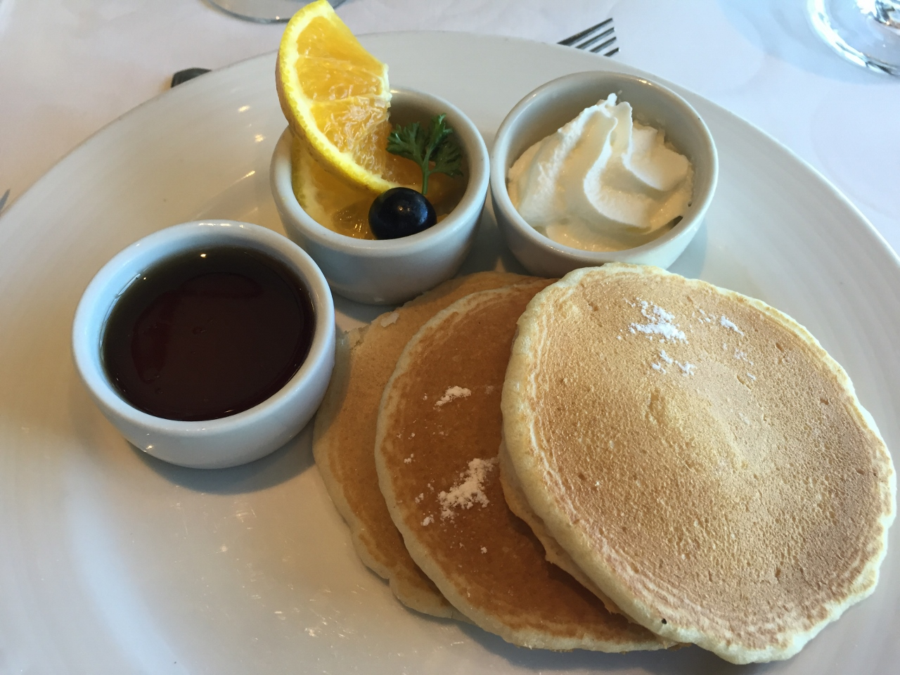 Fluffy pancakes with syrup and cream are on the menu for breakfast in the Empire Dining Room on Carnival Cruise Line.