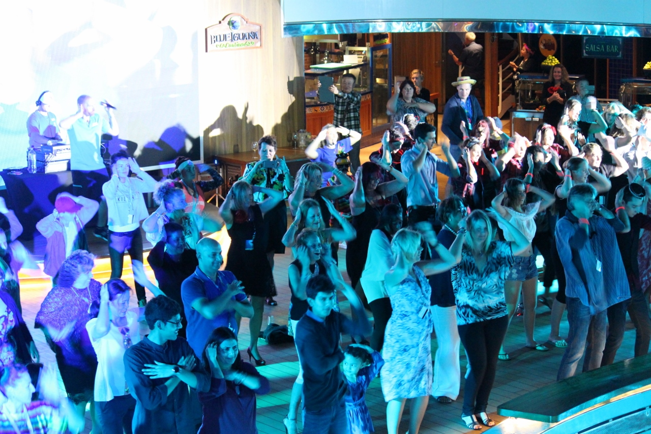 Carnival Spirit guests perform the Macarena, led by Cruise Director Eli Sharplin, up on pool deck.