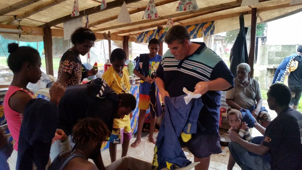 Cruise travellers hand out clothing to Vanuatu familiar affected by Cyclone Pam in 2015.