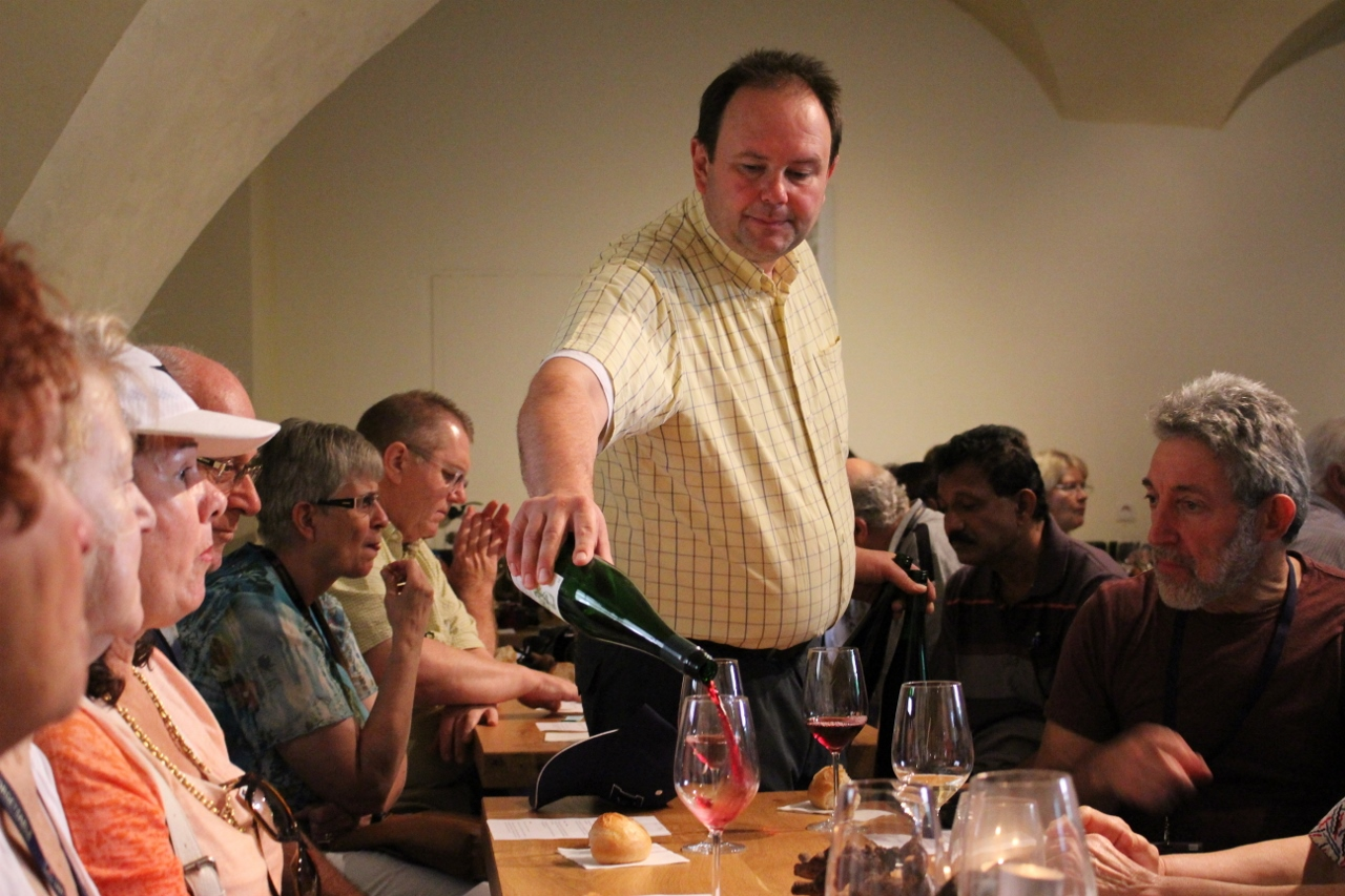 Nathan Waks (seated right) oversees the pouring of a red wine from the local fields.