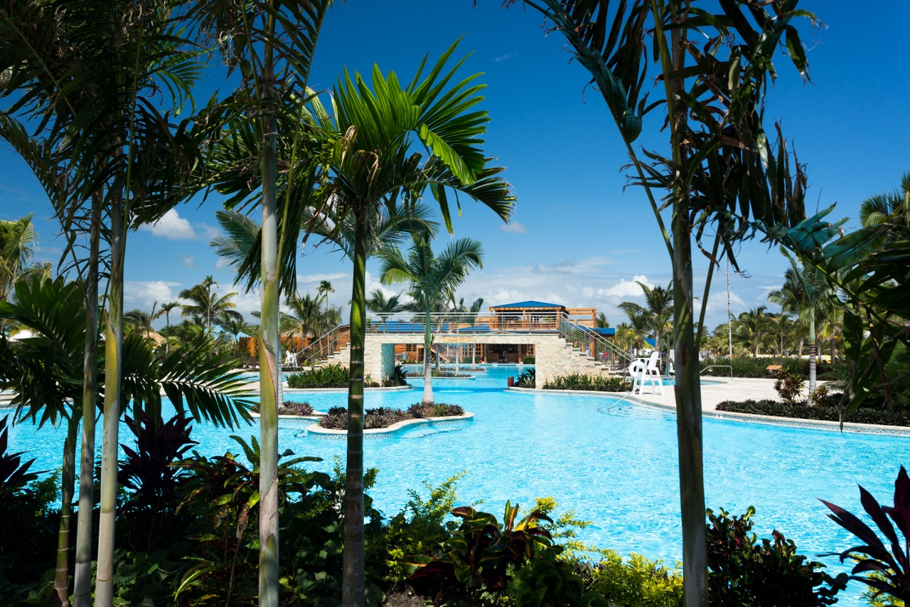 A sizeable lagoon style pool is surrounded by seating, plants and trees, dining, shopping and luxury poolside cabanas.